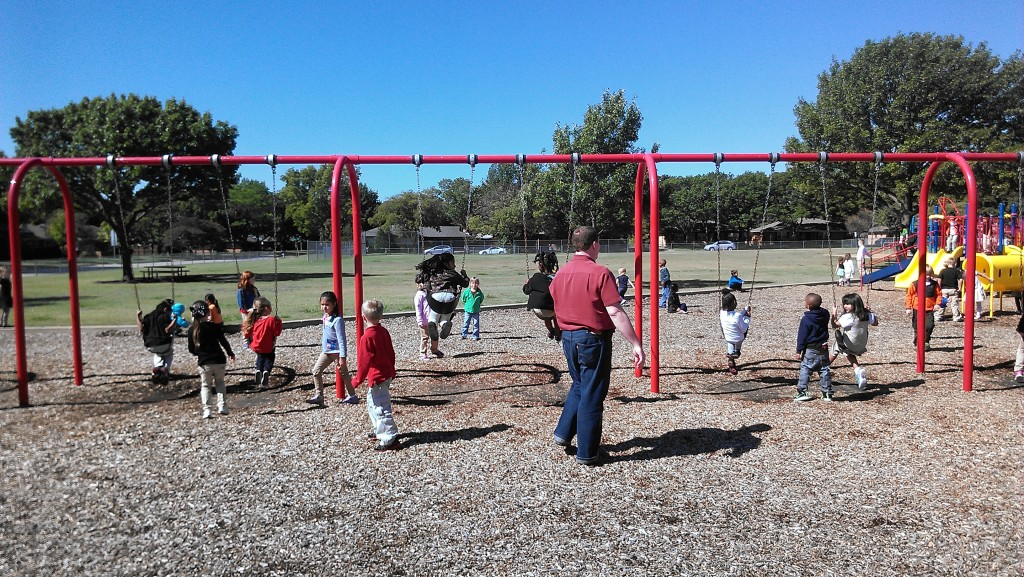 "We joined the kindergarteners for recess and all the children started calling for ""Dr. Manders"" to push them on the swings!"